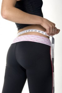 fit young woman with great buns measuring her waist